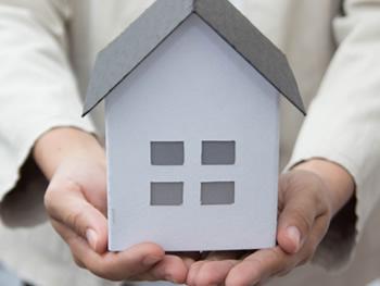 家の模型を大切そうに抱える手の写真